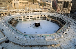 """(FILES) This file photo taken on March 05, 2020 shows the white-tiled area surrounding the Kaaba, inside Mecca's Grand Mosque, empty of worshippers. - Saudi Arabia announced it would hold a """"very limited"""" hajj this year owing to the coronavirus pandemic, with pilgrims already in the kingdom allowed to take part. (Photo by ABDEL GHANI BASHIR / AFP)"""