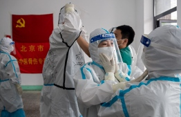 """Medics from Beijing Fengsheng Special Hospital of Traditional Medical Traumatology and Orthopaedics prepare for their shift at the Jinrong Street testing site, inside a room where a Communist Party flag and a piece of red tissue with words that reads """"Beijing Fengsheng Special Hospital of Traditional Medical Traumatology and Orthopaedics"""" (back on wall) in Beijing on June 24, 2020. (Photo by NICOLAS ASFOURI / AFP)"""