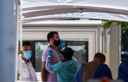 """A medical personnel member takes samples on a man at a """"walk-in"""" and """"drive-through"""" coronavirus testing site in Miami Beach, Florida on June 24, 2020. (Photo by CHANDAN KHANNA / AFP)"""