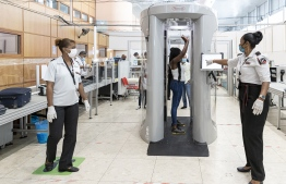 "An airport security officer gestures as a passenger passes through a millimeter wave scanner to check for contraband at a security checkpoint in the Felix Eboue Airport in Matoury, near Cayenne, on June 17, 2020. - Guyane authorities have equipped the Felix Eboue airport with two  millimeter wave scanner whole-body imaging devices as part of the fight against ""mule"" smuggling, in which people transport contraband on their person, including ingested packages of narcotics. (Photo by jody amiet / AFP)"