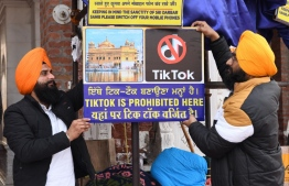 """(FILES) In this file photo taken on February 10, 2020 Sikh volunteers hang a sign reading 'Tiktok is prohibited here', at the Golden Temple in Amritsar. - TikTok on June 30 denied sharing information on Indian users with the Chinese government, after New Delhi banned the wildly popular app citing national security and privacy concerns. """"TikTok continues to comply with all data privacy and security requirements under Indian law and have not shared any information of our users in India with any foreign government, including the Chinese Government,"""" said the company, which is owned by China's ByteDance. (Photo by NARINDER NANU / AFP)"""
