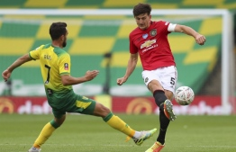 Manchester United's English defender Harry Maguire (R) plays the ball under pressure from Norwich City's German midfielder Lukas Rupp (L) during the English FA Cup quarter-final football match between Norwich City and Manchester United at Carrow Road in Norwich, eastern England on June 27, 2020. (Photo by Catherine Ivill / POOL / AFP) / RESTRICTED TO EDITORIAL USE. No use with unauthorized audio, video, data, fixture lists, club/league logos or 'live' services. Online in-match use limited to 120 images. An additional 40 images may be used in extra time. No video emulation. Social media in-match use limited to 120 images. An additional 40 images may be used in extra time. No use in betting publications, games or single club/league/player publications. /