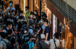 Police stop and search a man (centre R) after they entered a shopping mall to disperse people attending a lunchtime rally in Hong Kong on June 30, 2020, as China passed a sweeping national security law for the city. - China passed a sweeping national security law for Hong Kong, a historic move that critics and many western governments fear will smother the finance hub's freedoms and hollow out its autonomy. PHOTO: ANTHONY WALLACE / AFP