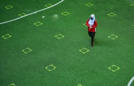 A student walks across a field with social distancing floor markers following the brief reopening of schools in Male' from July 1. PHOTO: NISHAN ALI/ MIHAARU