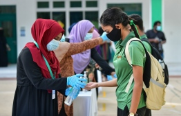 A student sanitising her hands at the gate. The number of virus cases in Maldives increased with the easing of lockdown measures in the transition to the 'new normal'. PHOTO: MIHAARU