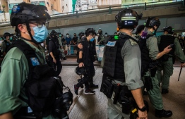 Riot police detain a man (C) as they clear protesters taking part in a rally against a new national security law in Hong Kong on July 1, 2020, on the 23rd anniversary of the city's handover from Britain to China. - Hong Kong police made the first arrests under Beijing's new national security law on July 1 as the city greeted the anniversary of its handover to China with protesters fleeing water cannon. (Photo by DALE DE LA REY / AFP)