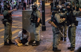 Riot police detain a man after they cleared protesters taking part in a rally against a new national security law in Hong Kong on July 1, 2020, on the 23rd anniversary of the city's handover from Britain to China. - Hong Kong police made the first arrests under Beijing's new national security law on July 1 as the anniversary of the city's handover to China was met by thousands defying a ban on protests. (Photo by DALE DE LA REY / AFP)