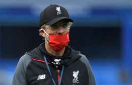 (FILES) In this file photo taken on June 21, 2020 Liverpool's German manager Jurgen Klopp wearing a face mask comes out for the warm up during the English Premier League football match between Everton and Liverpool at Goodison Park in Liverpool, north west England. - The delay to Liverpool's title celebrations caused by the coronavirus was just the latest twist in the tale of the Reds' 30-year wait to be crowned champions of England. A stunning run of 26 wins and one draw from their opening 27 games of the Premier League season ensured Jurgen Klopp's men were champions-elect long before football was shut down in March. (Photo by PETER POWELL / POOL / AFP) / RESTRICTED TO EDITORIAL USE. No use with unauthorized audio, video, data, fixture lists, club/league logos or 'live' services. Online in-match use limited to 120 images. An additional 40 images may be used in extra time. No video emulation. Social media in-match use limited to 120 images. An additional 40 images may be used in extra time. No use in betting publications, games or single club/league/player publications. /
