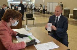 Russian President Vladimir Putin shows his passport to a member of a local electoral commission as he arrives to cast his ballot in a nationwide vote on constitutional reforms at a polling station in Moscow on July 1, 2020. (Photo by Alexei Druzhinin / SPUTNIK / AFP)