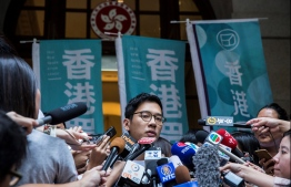 (FILES) In this file photo taken on October 24, 2017 pro-democracy activist Nathan Law speaks to the media outside the Court of Final Appeal after he and Joshua Wong's (not pictured) bail application were successful at Hong Kong's highest court. - Nathan Law, one of Hong Kong's most prominent young democracy activists, announced on July 2, 2020 he had fled overseas in response to Beijing imposing a sweeping security law on the city. (Photo by ISAAC LAWRENCE / AFP)