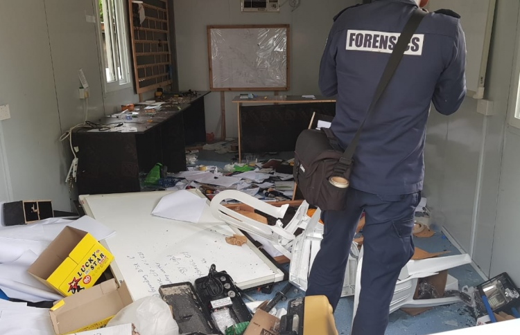 A Police officer from the Forensics department inspects a building vandalised during a protest held by expatriate officers on B. Bodufinolhu over six months of unpaid salaries. PHOTO/POLICE