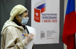 An elderly woman wearing a face mask and gloves - a measure against the spread of the coronavirus disease - prepares to cast her ballot in a nationwide vote on constitutional reforms at a polling station in Saint Petersburg on July 1, 2020. (Photo by OLGA MALTSEVA / AFP)