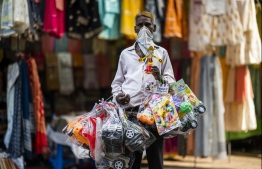 A vendor selling toys waits for customers in a market area in New Delhi on July 5, 2020. (Photo by Jewel SAMAD / AFP)