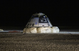 (FILES) In this file photo taken on December 22, 2019 This NASA photo shows the Boeing CST-100 Starliner spacecraft after it landed in White Sands, New Mexico. - NASA has drawn up a list of 80 recommendations that US aerospace giant Boeing will have to address before attempting to refly its Starliner space capsule, following the failure of an uncrewed test last year. (Photo by Bill INGALLS / NASA / AFP) /