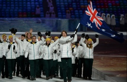 """(FILES) File photo taken on February 7, 2014 shows Australia's flag bearer, snowboarder Alex Pullin leading his national delegation during the opening ceremony of the Sochi Winter Olympics at the Fisht Olympic Stadium in Sochi. - Former world snowboarding champion Alex """"Chumpy"""" Pullin died on July 8, 2020 aged 32 after a spearfishing accident off Australia's Gold Coast, Olympic officials said. (Photo by ANDREJ ISAKOVIC / AFP FILES / AFP)"""