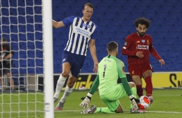 Brighton's Australian goalkeeper Mathew Ryan blocks an attempt by Liverpool's Egyptian midfielder Mohamed Salah (R) during the English Premier League football match between Brighton and Hove Albion and Liverpool at the American Express Community Stadium in Brighton, southern England on July 8, 2020. (Photo by PAUL CHILDS / POOL / AFP) / RESTRICTED TO EDITORIAL USE. No use with unauthorized audio, video, data, fixture lists, club/league logos or 'live' services. Online in-match use limited to 120 images. An additional 40 images may be used in extra time. No video emulation. Social media in-match use limited to 120 images. An additional 40 images may be used in extra time. No use in betting publications, games or single club/league/player publications. /