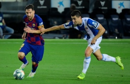 Barcelona's Argentine forward Lionel Messi (L) vies with Espanyol's Spanish midfielder Marc Roca during the Spanish League football match between Barcelona and Espanyol at the Camp Nou stadium in Barcelona on July 8, 2020. (Photo by LLUIS GENE / AFP)