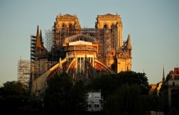 """(FILES) A file photo taken on April 14, 2020 shows the Paris' Cathedral Notre Dame at the sunrise on the eve of the first anniversary of the violent fire who destroyed a large part of the monument, on the twenty-nineth day of a lockdown in France to stop the spread of the  COVID-19, (the novel coronavirus). - New French Minister of Culture Roselyne Bachelot estimated on July 9, 2020 that a """"broad consensus"""" existed to reconstruct """"identically"""" the spire of Notre-Dame de Paris cathedral, while an advisory committee will meet on the same day to discuss the matter. (Photo by THOMAS COEX / AFP)"""