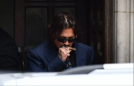 """US actor Johnny Depp gestures as he leaves on the third day of his libel trial against News Group Newspapers (NGN), at the High Court in London, on July 9, 2020. - Hollywood superstar Johnny Depp testified in a London court on Thursday that he was so often high or strung out on drugs that he was """"in no condition"""" to hurt his ex-wife Amber Heard. Depp is suing the publishers of The Sun and the author of the article for the claims that called him a """"wife-beater"""" in April 2018. (Photo by JUSTIN TALLIS / AFP)"""