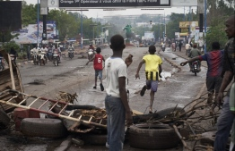 """People run away at the arrival of the riot police as protesters set barricades to block the circulation on the Martyrs bridge of Bamako on July 11, 2020. - Malian Prime Minister Boubou Cisse on July 11, 2020 vowed to rapidly form a government """"open to facing the challenges of the day"""", adding that four more people had died in the country's worst civil unrest in years. PHOTO: MICHELE CATTANI / AFP"""