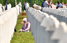 A Bosnian Muslim woman, survivor of the 1995 Srebrenica massacre, sits near tombstones of her relatives, at the Potocari memorial cemetery, a village just outside Srebrenica on July 11, 2020. - Nine sets of newly identified Bosnian Muslim victims were layed to their final resting place during the ceremony marking the 25th anniversary of the massacre in Srebrenica. During the offensive on the UN safe heaven area of Srebrenica by Bosnian Serbs in July 1995, more than 8,000 Bosnian non-Serbs went missing, only to be found burried in mass graves, years after the war ended. (Photo by ELVIS BARUKCIC / AFP)