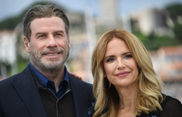 """(FILES) In this file photo taken on May 15, 2018 US actor John Travolta (L) and his wife US actress Kelly Preston pose during a photocall for the film """"Gotti"""" at the 71st edition of the Cannes Film Festival in Cannes, southern France. - Kelly Preston, US actress and wife of US actor John Travolta, died after a battle with breast cancer at the age of 57, US media reported on July 12, 2020. (Photo by Anne-Christine POUJOULAT / AFP)"""