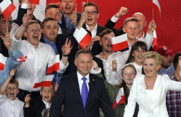 Polish President Andrzej Duda flashes V-signs after addressing supporters with his wife Agata as exit poll results were announced during the presidential election in Pultusk, Poland, on July 12, 2020. - Poland's right-wing head of state Andrzej Duda was ahead by a tiny margin in the presidential run-off against Warsaw's liberal mayor, an exit poll on on July 12, 2020 showed, starting a tense wait for the official results (Photo by JANEK SKARZYNSKI / AFP)