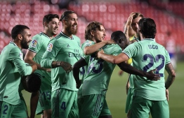 Real Madrid's French defender Ferland Mendy (3R) celebrates with teammates after scoring  during the Spanish league football match Granada FC vs Real Madrid CF at Nuevo Los Carmenes stadium in Granada on July 13, 2020. (Photo by JORGE GUERRERO / AFP)
