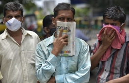 In this picture taken on July 9, 2020, a man holds a newspaper to cover his face in the absence of his facemask during the COVID-19 coronavirus pandemic, in Bangalore. - Indian police are having a field day handing out fines to people who do not wear a mask during the coronavirus pandemic. Some object but many people just cannot get used to the accessory that has come to symbolise the new normal. India now has almost 880,000 cases and more than 23,000 dead and experts say the peak is still weeks away. But rich and poor say they feel awkward or uncomfortable with a mask. (Photo by Manjunath Kiran / AFP)