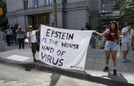 Protestors gather outside court as Ghislaine Maxwell is set to make her first court appearance on July 14, 2020 at the US District Court for the Southern District of New York, on a video link from her cell at the Metropolitan Detention Center in Brooklyn, over sex-trafficking charges tied to her former boyfriend Jeffrey Epstein in New York. - British socialite Ghislaine Maxwell pleaded not guilty in a New York court Tuesday to sex trafficking minors for her former partner, the financier Jeffrey Epstein. The 58-year-old denied six charges related to alleged crimes committed by Epstein, a well-connected sex offender who killed himself in prison while awaiting trial last summer. (Photo by TIMOTHY A. CLARY / AFP)