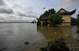 A general views shows Sansheng Temple flooded by the rising water level of the Yangtze River in Jiujiang in China's central Jiangxi province on July 15, 2020. - The vast Yangtze drainage area has been lashed by torrential rains since last month, leaving 141 people dead or missing and forcing the evacuation of millions more across several provinces. (Photo by Hector RETAMAL / AFP)