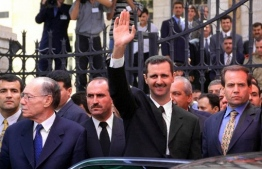 (FILES) A file photo taken on July 17, 2000 shows Syria's new President Bashar al-Assad (C) waving to supporters outside the parliament in Damascus 17 July 2000, after taking the oath of office. - Bashar al-Assad's rise to power after three decades of his father's iron-fisted rule raised hope of democratic opening. But 20 years later, Syria is isolated and war-ravaged. Crumbling under a stinging economic downturn, Western sanctions and nine years of war, Syria today is a far cry from the vision Assad projected when he was propelled to the presidency a month after his father Hafez died on June 10, 2000. (Photo by Louai Beshara / AFP)