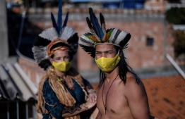Angoho (L) and her husband Hayo, leader and chief of the Pataxo Hahahae ethnic group, respectively, wear face masks at the Vila Vitoria favela on the outskirts of Belo Horizonte, state of Minas Gerais, Brazil, on July 8, 2020 amid the COVID-19 novel coronavirus pandemic. - Angoho and her relatives have been displaced twice from their land. First due to a water crisis caused by the spread of eucalyptus afforestation and in 2019 because the rupture of a mud dam belonging to the mining company Vale sent tons of toxic waste into the Paraopeba River from which they depended on. Now, Angoho and little more than ten Pataxo Hahahae families are struggling to survive the COVID-19 pandemic in a place where they feel they don't belong -the city. (Photo by DOUGLAS MAGNO / AFP)