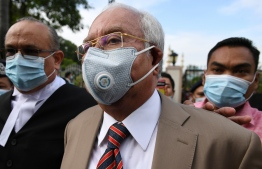Malaysia's former prime minister Najib Razak (C) arrives at the Duta Court complex awaiting a verdict in his corruption trial in Kuala Lumpur on July 28, 2020. - A Malaysian court will hand down its verdict in Najib Razak's first corruption trial on July 28 following a long-running case probing the former prime minister's role in the multi-billion-dollar 1MDB scandal. (Photo by Mohd RASFAN / AFP)