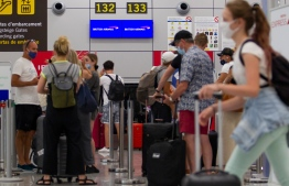 British tourists wait to check in for a flight to London at the airport in Palma de Mallorca on July 27, 2020. - Tour operator TUI has cancelled all British holidays to mainland Spain from today until August 9, after the UK government's decision to require travellers returning from the country to quarantine. (Photo by JAIME REINA / AFP)