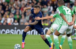 (FILES) In this file photo taken on March 08, 2020 Real Madrid's Dominican forward Mariano Diaz (C) vies for the ball with Real Betis' Spanish defender Marc Bartra (R) during the Spanish league football match between Real Betis and Real Madrid CF at the Benito Villamarin stadium in Seville. - Real Madrid forward Mariano has tested positive for coronavirus, the La Liga champions announced on Jaly 28, 2020. (Photo by CRISTINA QUICLER / AFP)