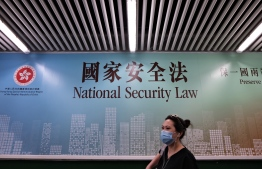 A woman walks past a poster for the National Security Law in Hong Kong on July 28, 2020. (Photo by Anthony WALLACE / AFP)