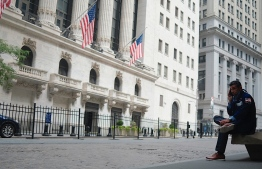 (FILES) In this file a trader makes a phone call outside the New York Stock Exchange (NYSE) on July 20, 2020 at Wall Street in New York City. - Wall Street stocks dropped in opening trading on July 30, 2020 following data showing an historic drop in US growth in the second quarter and higher weekly jobless claims. Shortly after the opening bell, the Dow Jones Industrial Average was down 1.2 percent at 26,215.34.The broad-based S&P 500 fell 1.1 percent to 3,223.42, while the tech-rich Nasdaq Composite Index shed 0.9 percent to 10,446.97. (Photo by Johannes EISELE / AFP)