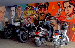 In this picture taken on July 21, 2020, two-wheelers are seen parked in front of a wall mural with images of Bollywood actors, under a road bridge in Mumbai. - India's coronavirus lockdown made little difference to Bollywood superstars but for the industry's vast army of low-paid, unskilled workers it meant unemployment, hunger and homelessness -- with no end in sight even as shootings gradually resume. PHOTO: SUJIT JAISWAL / AFP