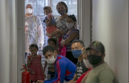 Patients await medical care at the Medical Care Ship Unit UBS, docked at the riveside community of Galileia, on the river Soiai, municipality of Melgaco in Marajo Island, state of Para, Brazil, on July 29, 2020 during the COVID-19 coronavirus pandemic. - The UBS ship is crossing the rivers of Melgaco attending more than five thousand people of more than 100 riverside communities of the region carrying out COVID-19 tests and providing all sort of medical treatments. PHOTO: TARSO SARRAF / AFP