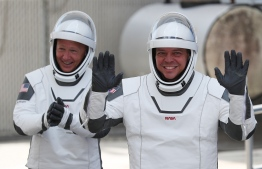 (FILES) In this file photo taken on May 30, 2020, NASA astronauts Bob Behnken (R) and Doug Hurley walk out of the Operations and Checkout Building on their way to the SpaceX Falcon 9 rocket with the Crew Dragon spacecraft on launch pad 39A at the Kennedy Space Center in Cape Canaveral, Florida. - The first US astronauts to reach the International Space Station on an American spacecraft in nearly a decade might not come home this weekend as scheduled because of Hurricane Isaias, NASA said July 31, 2020. PHOTO: JOE RAEDLE / GETTY IMAGES NORTH AMERICA / AFP