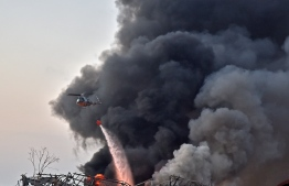 EDITORS NOTE:  / A helicopter puts out a fire at the scene of an explosion at the port of Lebanon's capital Beirut on August 4, 2020. (Photo by STR / AFP)