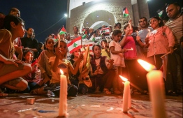 Palestinians attend a candle light vigil in Rafah in the southern Gaza Strip on August 5, 2020, in support of Lebanon a day after a blast in a warehouse in the port of the Lebanese capital sowed devastation across entire city neighbourhoods. (Photo by SAID KHATIB / AFP)