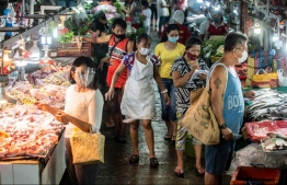 People wearing masks shop for fresh food at a market in Manila on August 6, 2020. - The Philippines plunged into recession after its biggest quarterly contraction in four decades, data showed on August 6, as the economy reels from COVID-19 coronavirus lockdowns that have wrecked businesses and thrown millions out of work. PHOTO: LISA MARIE DAVID / AFP
