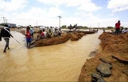 Sudanese men gather at a damaged road, after torrential rain lead to landslides and flash floods, in the town of Umm Dawan Ban, southeast of the capital Khartoum on August 2, 2020. PHOTO: ASHRAF SHAZLY / AFP