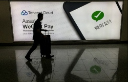 This photo taken on August 21, 2017 shows a man walking at Hong Kong's international airport past an advertisement for the WeChat social media platform owned by China's Tencent company. - US President Donald Trump on August 6, 2020 ordered sweeping restrictions against Chinese-owned social media stars TikTok and WeChat, which could strangle their ability to operate in the United States. (Photo by RICHARD A. BROOKS / AFP)