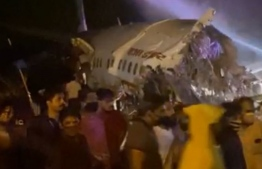 A passenger plane that crashed after it overshot the runway is seen at Calicut International Airport in Karipur, southern state of Kerala, India, August 7, 2020, in this still image obtained from a video.