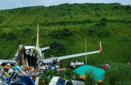 Officials inspect the wreckage of an Air India Express jet at Calicut International Airport in Karipur, Kerala, on August 8, 2020. - Fierce rain and winds lashed a plane carrying 190 people before it crash-landed and tore in two at an airport in southern India, killing at least 18 people and injuring scores more, officials said on August 8. (Photo by Arunchandra BOSE / AFP)