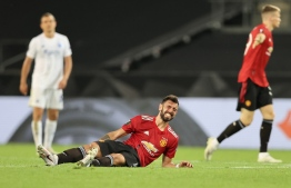 Manchester United's Portuguese midfielder Bruno Fernandes reacts after an injury during the UEFA Europa League quarter-final football match between Manchester United and FC Copenhagen at the RheinEnergieStadion, in Cologne, western Germany, on August 10, 2020. (Photo by WOLFGANG RATTAY / POOL / AFP)