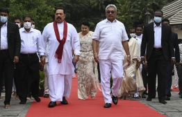 Sri Lanka's President Gotabaya Rajapakse (2R) and Prime Minister Mahinda Rajapakse (2L) leave after the new cabinet swearing-in ceremony at the Buddhist Temple of the Tooth in the ancient hill capital of Kandy, some 116 km from Colombo on August 12, 2020. - Sri Lanka president Gotabaya Rajapaksa retained the powerful defence portfolio and gave other key jobs to his close family in a 26-member cabinet appointed on August 12. (Photo by LAKRUWAN WANNIARACHCHI / AFP)